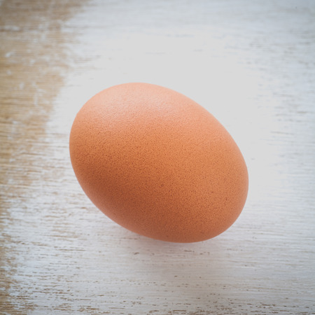 chicken egg: Healthy food brown chicken egg on white wood table background Stock Photo