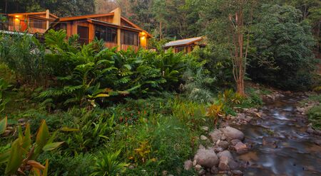Summer house beside waterfall at mountain forest