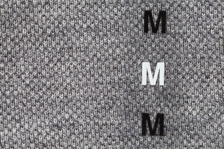 backcloth: Close - up plastic size tag on shirt Stock Photo