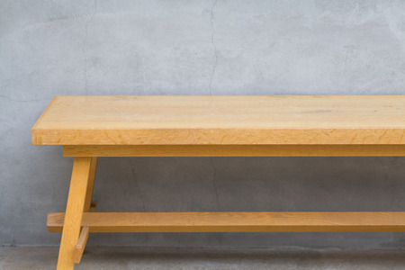wood bench: Brown wood bench and concrete wall background