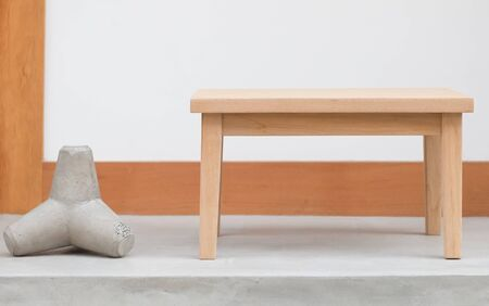 wood table: Simple brown wood table and white concrete wall Stock Photo