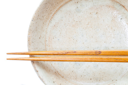 celadon green: Brown wood chopsticks and white ceramic on white background