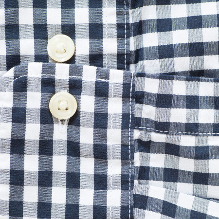 white sleeve: Close - up Black and white check shirt sleeve and button