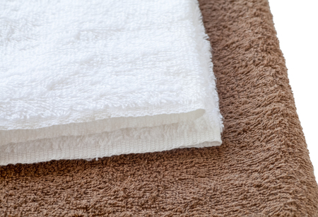 white towel: White clean towel on brown towel background Stock Photo