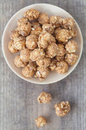 palomitas: Almond y palomitas caramal sobre fondo de madera