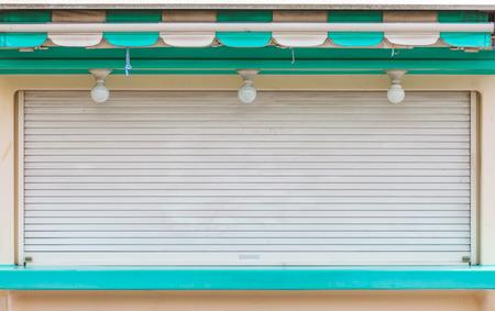 shop window: Metal window shutter closed at small shop Stock Photo