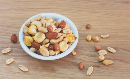 mixed nuts: Mixed nuts in small bowl on wood table