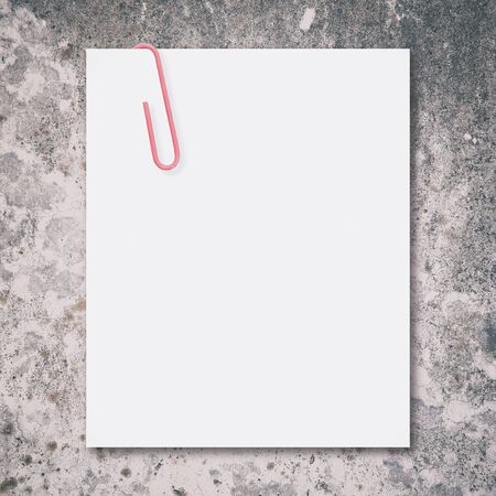 White blank space and red paper clip on stone background