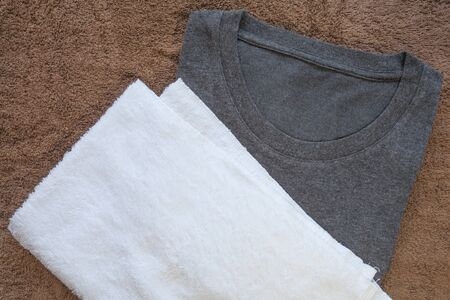black t shirt: White towel and black t - shirt on brown towel background