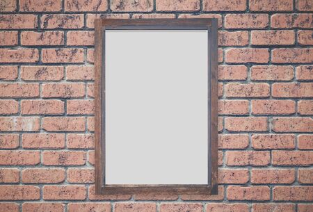 Brown wood picture frame on red brick wall