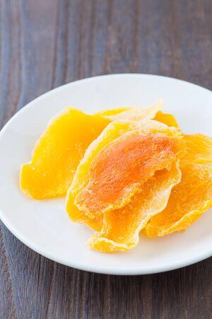 dehydrate: Piece of Dehydrated mango on white ceramic dish