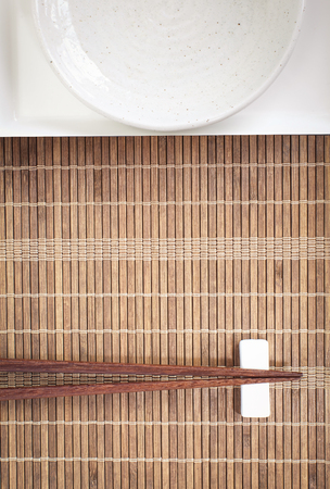 bamboo mat: Brown wood chopstick and white ceramic plate on bamboo mat Stock Photo