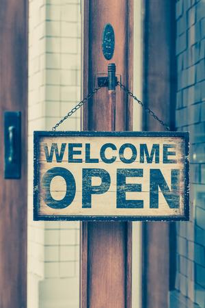 Wood open sign boaed hang on shop wood door