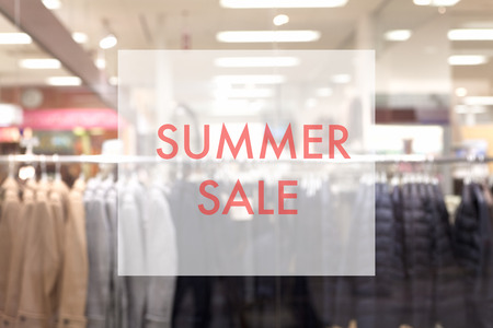 sale shop: Promotion poster on glass window at fashion clothes store