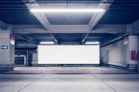 Parking garage underground interior with blank billboard Foto de archivo