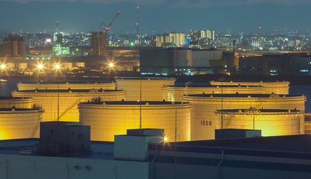 industrail: Oil tank at industrail zone and high building in the city in background