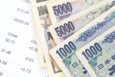 japanese currency: Close - up of Japanese currency yen bank notes and financial chart Stock Photo