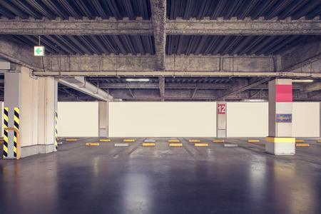 garage background: Parking garage underground interior with blank billboard Stock Photo