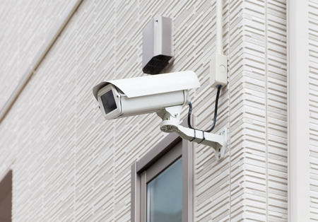 Video-Kamera-Sicherheitssystem an der Wand des Gebäudes Standard-Bild - 54889327