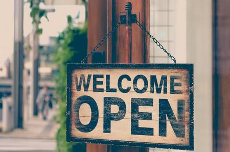 Caduta di legno aperta del cartello stradale sulla porta di legno del negozio, segno aperto, insegna aperta
