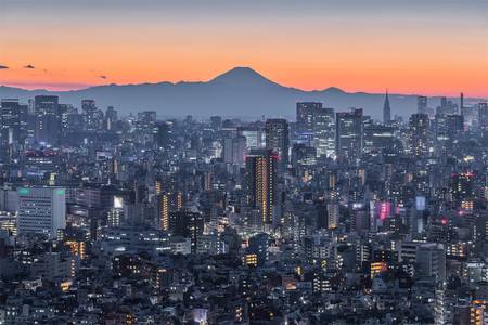 Tokyo night city view with Mountain Fuji. Mount Fuji lies about 100 kilometres south-west of Tokyo, and can be seen from there on a clear day.