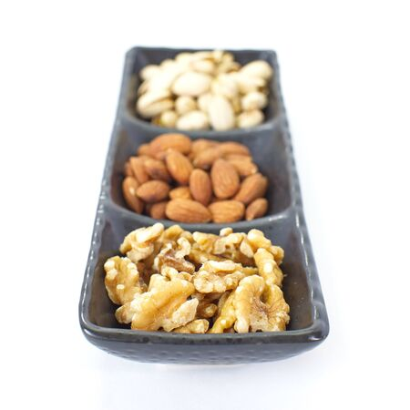 Assorted mixed nuts in black plate on white background 版權商用圖片