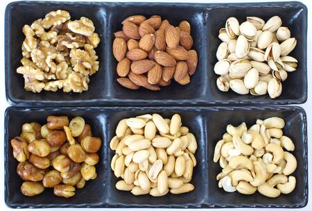Assorted mixed nuts in black plate on white background Stok Fotoğraf