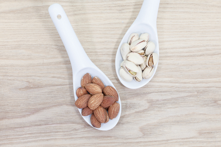 Assorted mixed nuts in white spoon on wood table background
