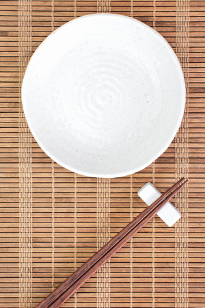 White ceramic plate and wood chopstick on brown bamboo plate mat