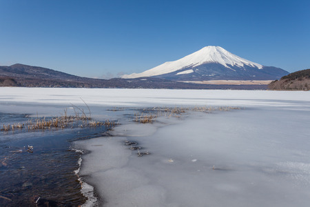 The water in Lake Yamanaka becomes ice during the winter and Mt.Fuji covered in snow 写真素材