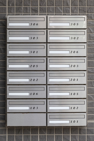 Metal letter box with room number at apartment building