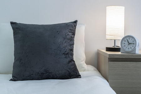 Gray cushions on the bed and lamp and alarm clock on the bedside table
