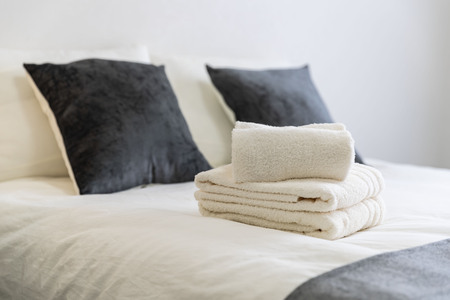 Clean white towels placed on the bed