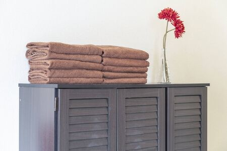 A brown towel pile placed on a wooden cabinet