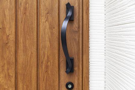 Entrance door handle close up. Lock and handle on the door. Reinforced door lock. Doorknob at a brown wood door
