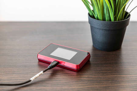 Pocket wifi with battery charger on brown wood table Stock Photo