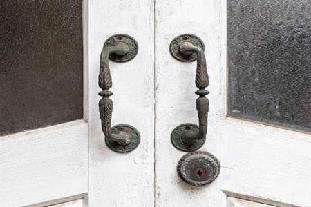 Close - up Old brass door handle and white wooden door