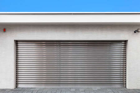 Automatic silver roller shutter doors on the ground floor of the house Standard-Bild