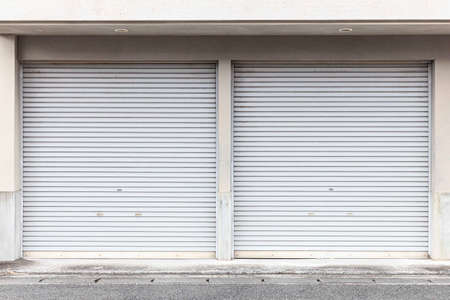 Automatic white roller shutter doors on the ground floor of the house