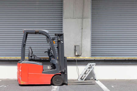 A forklift is parked in front of a warehouse in the industrial area