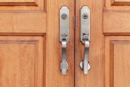 Antique iron door openers and dark brown wooden doors