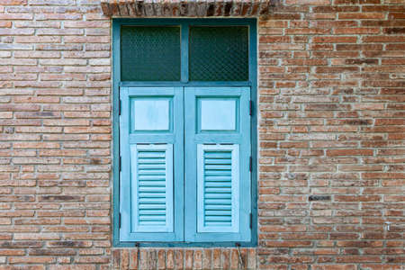 European antique blue wooden shutters window and brown stone brick wall