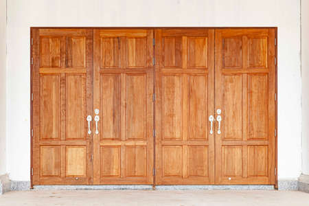 Large brown wooden door entrance and white cement wall Standard-Bild