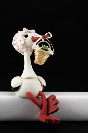 photography wooden doll in the shape of a stork carrying a baby basket Stock Photo - 4736699