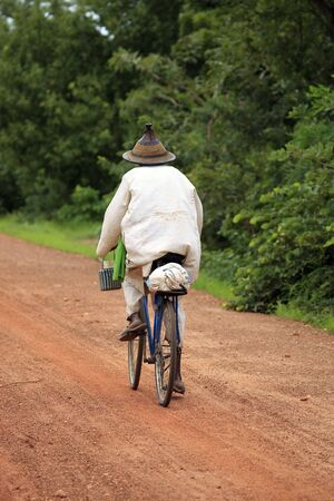 African man by bicycle by Carretra of land in Burkina Faso photo