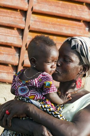 poor child: Country Bissa,Burkina Faso - August 9,2009 : Mother kissing her daughter, women of ethnic Bissa lovingly of his children. Editorial