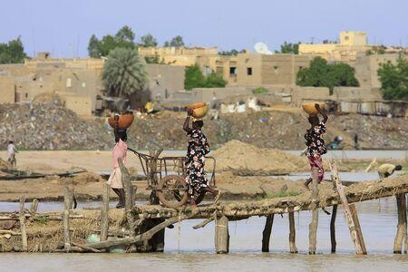Mopti, Mali - agosto 16,2009: la mujer transportar carga, el puerto de Mopti es el país más importante en el transporte de mercancías.