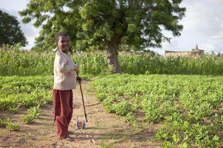 País Bissa, Burkina Faso - agosto 9,2009: hijo de Bissa étnica con juguetes caseros, falta de recursos agudiza el ingenio.