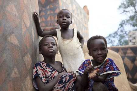 Tiebele,Burkina Faso - August 10,2009 : Gourounsi children are watching us on the visit of the village,are built with high walls to protect themselves from rival attacks.