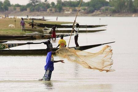 Mopti, Malí - agosto 16,2009: pesca de juventud en el río Níger, pesca en el río aún está en marcha en la forma tradicional por lanzar la red desde la orilla.